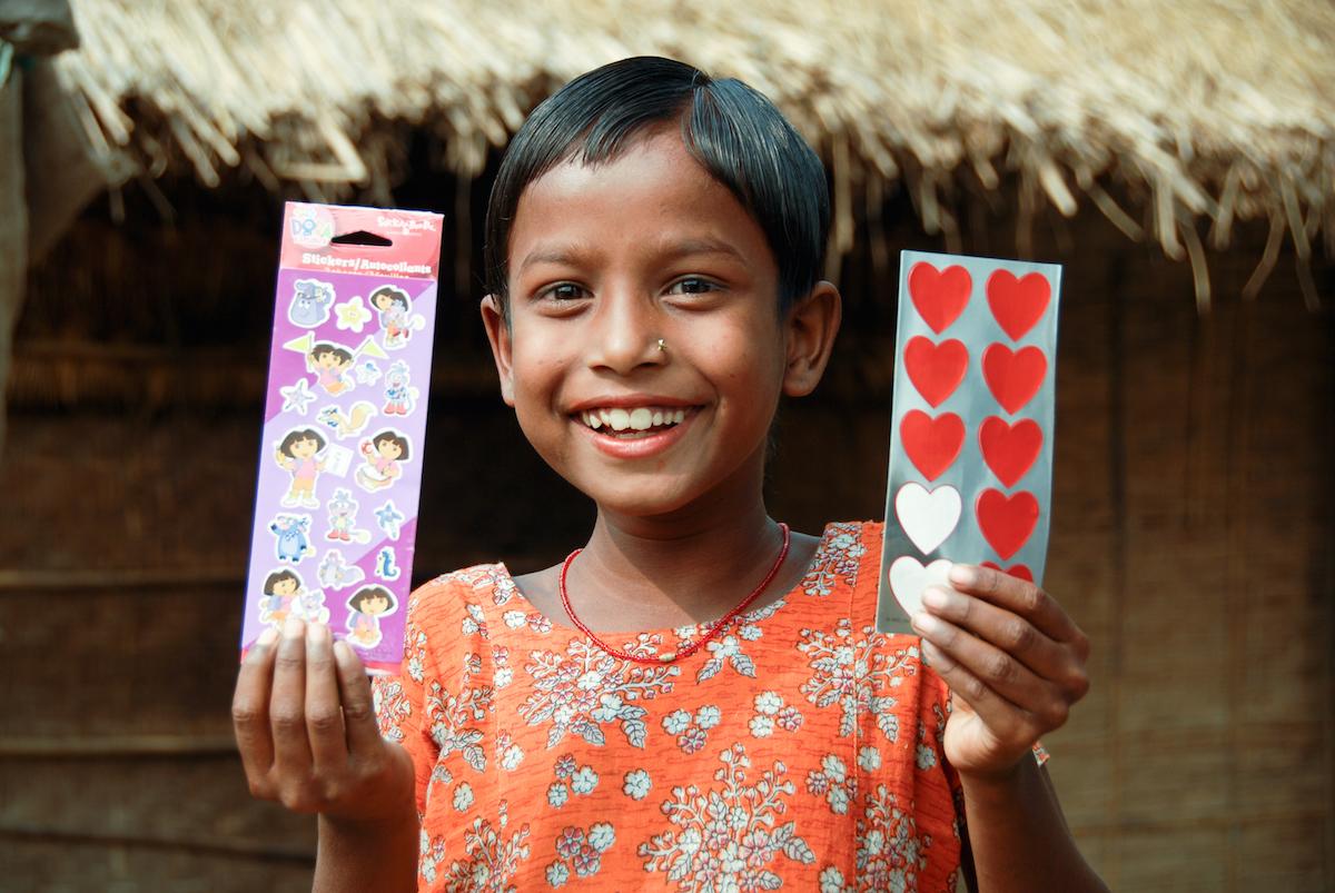 Mumun aus Bangladesh zeigt ihre Weihnachtsgrüße, die sie von ihren Spendern aus Kanada erhalten hat.