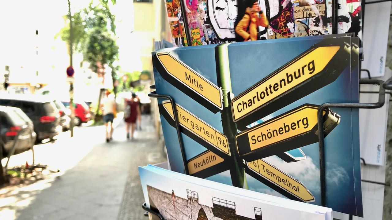 #Schulkrise in Berlin: Die Postkarte zeigt Straßenschilder mit Bezirksnamen, die in verschiedene Richtungen weisen