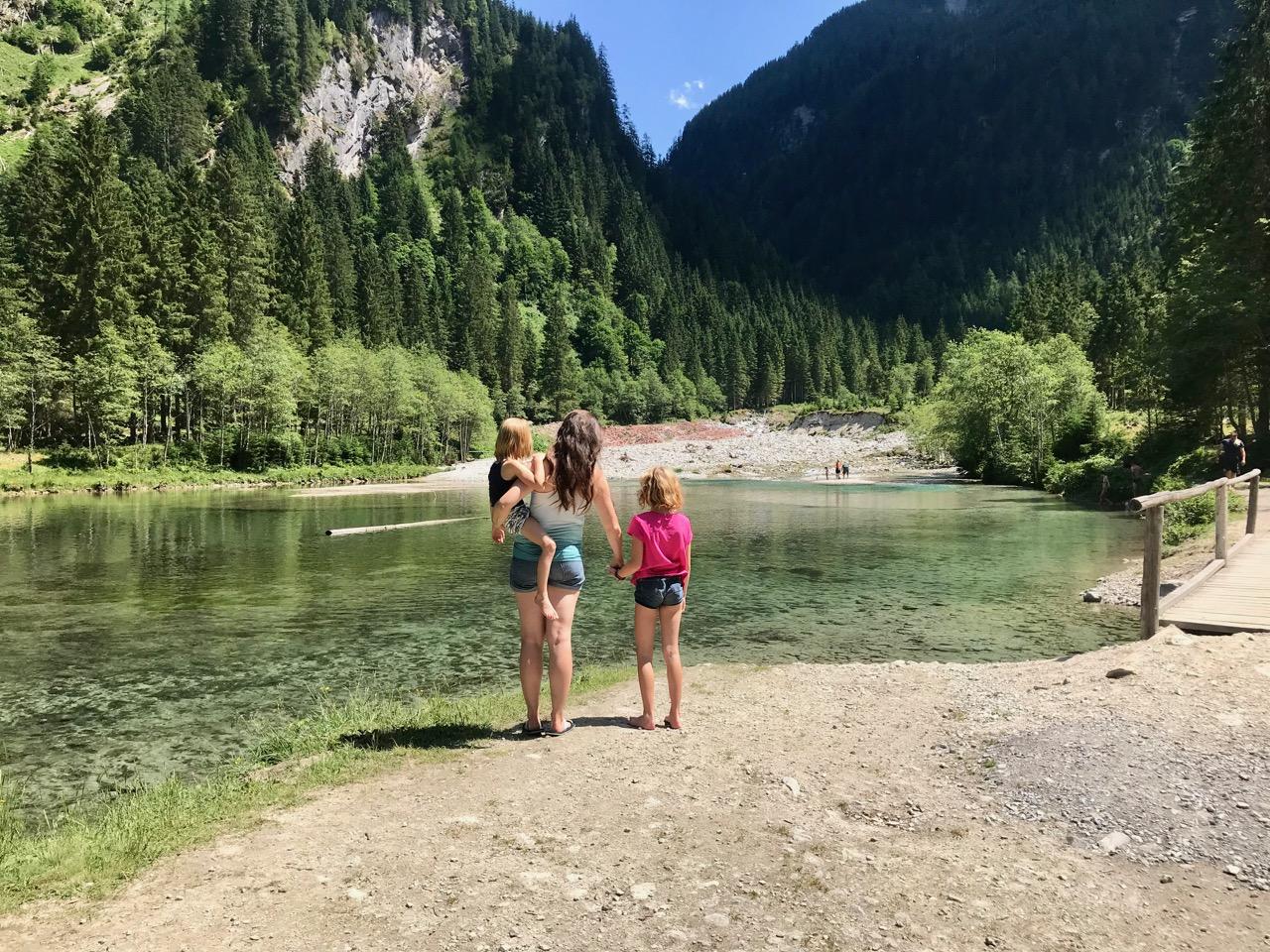 Frau mit langen Haaren steht an einem Bergsee. Ein Mädchen auf dem Arm, ein Mädchen an der Hand (Titelbild für Alle Artikel zur Haarspendeaktion #MamasZopf: Zu Fuß von Berlin nach Wien)