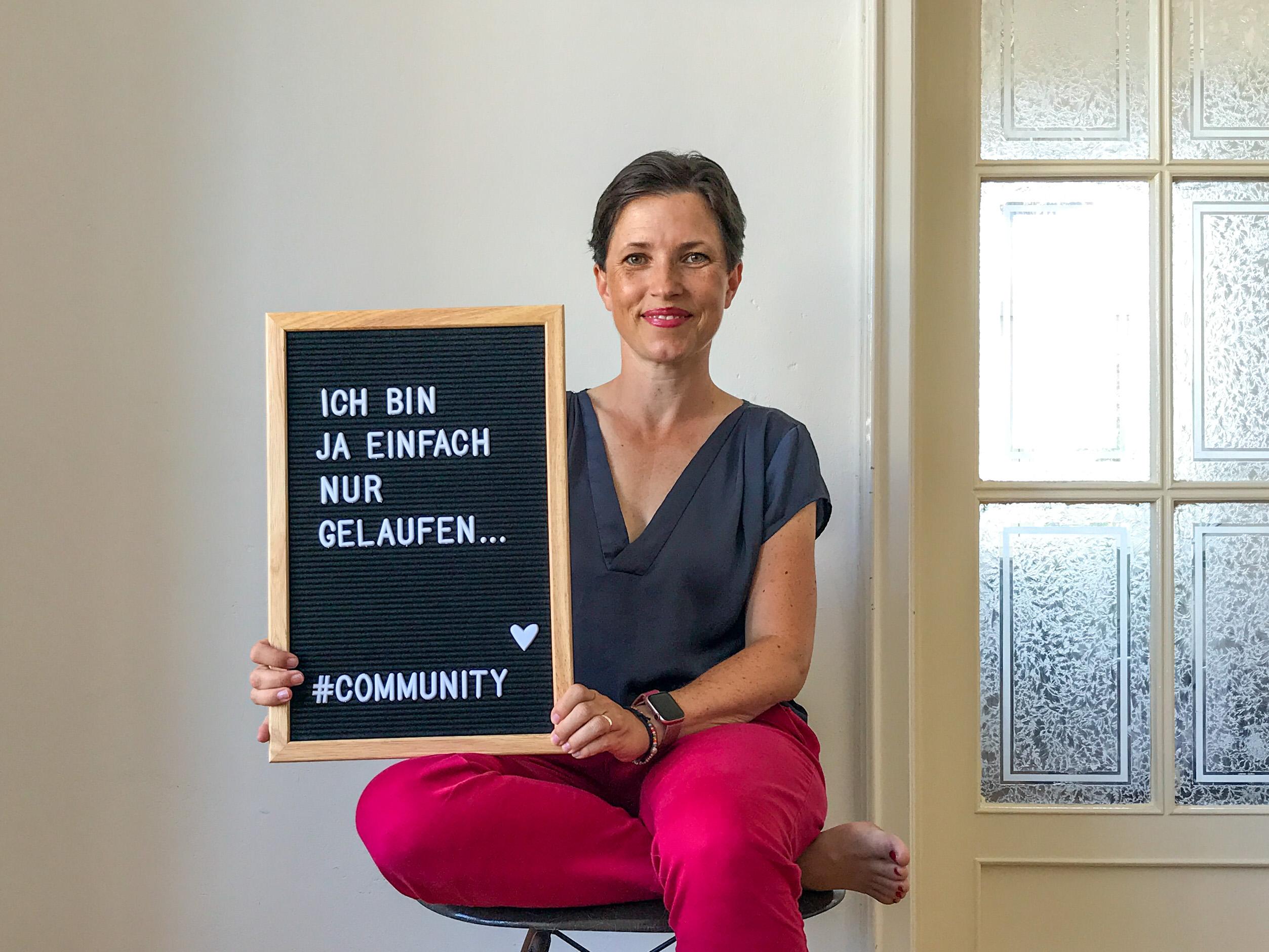 """Sophie sitzend auf einem Stuhl mit Tafel und Text: """"Ich bin ja einfach nur gelaufen... #Community und Herz-Symbol"""""""